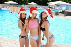 3 девушки в купальных костюмах и крышках Санта Клауса на selfie снимают предпосылку бассейна Стоковые Фото