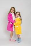 2 девушки в мантиях обнимая один другого Стоковое Изображение RF
