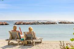 2 девушки в местах переднего ряда на пляже Стоковое Изображение