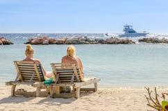 2 девушки в местах переднего ряда на пляже Стоковые Изображения