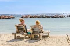 2 девушки в местах переднего ряда на пляже Стоковое Фото