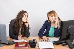 2 девушки в офисе говоря на мобильном телефоне на его столе Стоковое фото RF