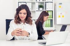 2 девушки в офисе проверяют их телефоны Стоковое Изображение