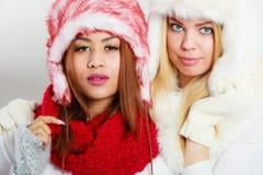 2 девушки в одежде зимы греют крышку Стоковые Фотографии RF