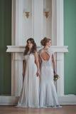 2 девушки в платьях свадьбы стоят рядом Стоковые Фотографии RF
