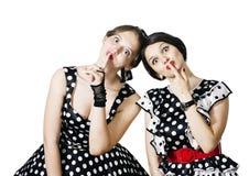 2 девушки в стиле штыря-вверх на белой предпосылке показывают жест безмолвия Стоковые Фотографии RF
