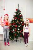 2 девушки в стойке костюмов рождества около Стоковое Фото