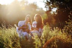 2 девушки в украинском национальном платье сидя на траве девушка Стоковые Изображения RF