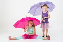 2 девушки в цветастых одеждах с покрашенными зонтиками Стоковое Фото