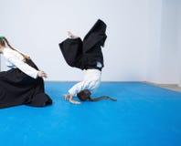 2 девушки в черном hakama практикуют айкидо на тренировке боевых искусств Стоковые Изображения RF