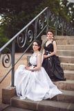 2 девушки в черно-белом усаживании на шагах Стоковое Изображение