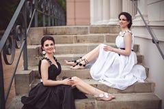 2 девушки в черно-белом усаживании на шагах Стоковые Изображения RF