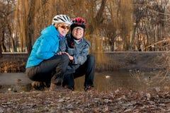 2 девушки в шлемах сидят на предпосылке вербы Стоковое фото RF