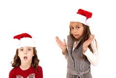 2 девушки в шляпах santa с выражениями потехи Стоковое Фото