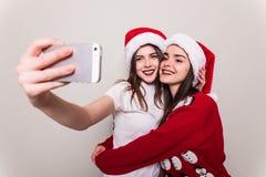 2 девушки в шляпе santa принимая selfie на телефоне Стоковое Фото