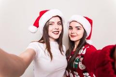 2 девушки в шляпе santa принимая selfie на телефоне Стоковая Фотография RF