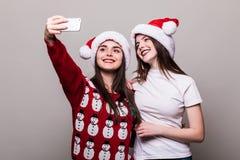 2 девушки в шляпе santa принимая selfie на телефоне Стоковые Изображения