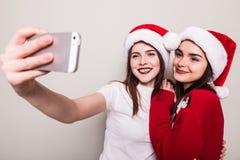 2 девушки в шляпе santa принимая selfie на телефоне Стоковое фото RF