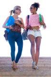2 девушки говоря и смеясь над в лестницах Стоковые Фотографии RF