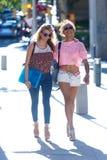 2 девушки говоря и смеясь над в улице Стоковое фото RF