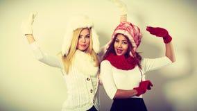 2 девушки греют одежду зимы имея потеху Стоковая Фотография