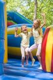 2 девушки гримасничая счастливо скачущ на раздувной батут Стоковое Изображение RF