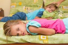 2 девушки лежат на кровати на противоположных сторонах Стоковая Фотография