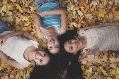 3 девушки лежа в листьях осени Стоковые Изображения RF