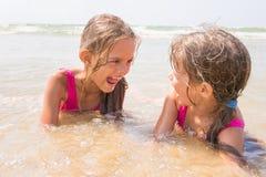 2 девушки лежа в мелководье и имеют потеху смотря один другого Стоковое Фото