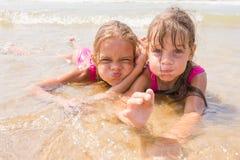 2 девушки лежа в мелководье и потеха претендуя стороны смотря в рамке Стоковое Фото