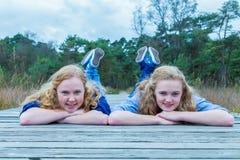 2 девушки лежа на деревянном пути в природе Стоковые Изображения