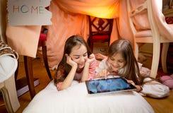 2 девушки лежа на поле на спальне и играя на цифровой таблице Стоковое фото RF