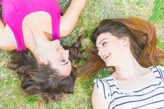 2 девушки лежа на траве и смеяться над Стоковая Фотография RF