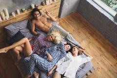 3 девушки лежа на man& x27; ноги s Стоковые Изображения RF