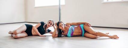 2 девушки лежа около поляка в студии тренировки Стоковое Изображение
