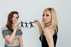2 девушки держат бумажные людей на белизне Стоковое Изображение