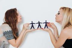 2 девушки держат бумажные людей на белизне Стоковые Фото