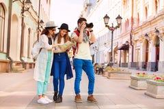 2 девушки держат карту и парня города с камерой Стоковые Фото