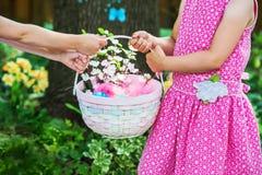 2 девушки держа корзину пасхи с цветками Стоковое Фото