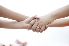 2 девушки держа руки друг к другу Стоковые Фотографии RF
