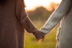 2 девушки держа руки совместно Стоковые Изображения