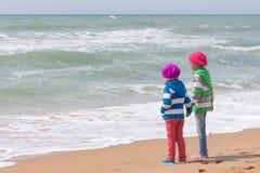 2 девушки держа руки стоя на пляже и смотря в расстояние Стоковые Изображения