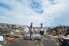 2 девушки держа руки стоя на тинной дороге смотря на свалку мусора Стоковое фото RF