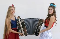2 девушки держа старый аккордеон Стоковые Изображения