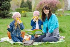 2 девушки есть банан на пикнике Стоковые Изображения