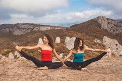 2 девушки делают йогу в ландшафте гор Стоковые Фото