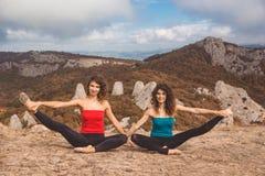 2 девушки делают йогу в ландшафте гор Стоковое Изображение