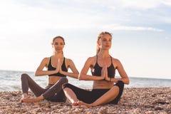 2 девушки делают йогу на пляже Стоковое Фото