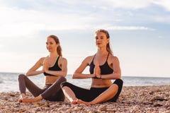2 девушки делают раздумье йоги на пляже Стоковые Изображения RF