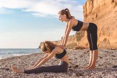 2 девушки делают pilates на пляже Стоковые Изображения